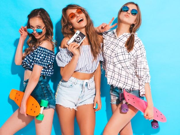 Drei sexy schöne stilvolle lächelnde mädchen mit bunten pennyskateboards. frauen in der karierten hemdkleidungsaufstellung des sommers. modelle, die fotos auf retro- fotokamera machen