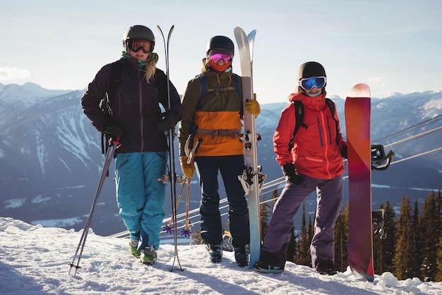 Drei skifahrer mit himmel, der auf schneelandschaft steht