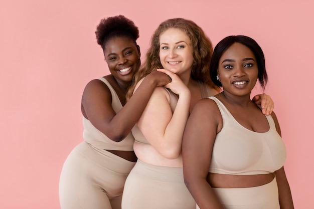 Drei smiley-frauen posieren, während sie einen körperformer tragen