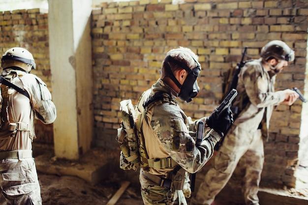 Drei soldaten sind im raum. sie bereiten sich auf einen kampf vor. jungs haben munition. einer von ihnen hat eine schwarze maske auf dem gesicht. sie sind bereit zu kämpfen.