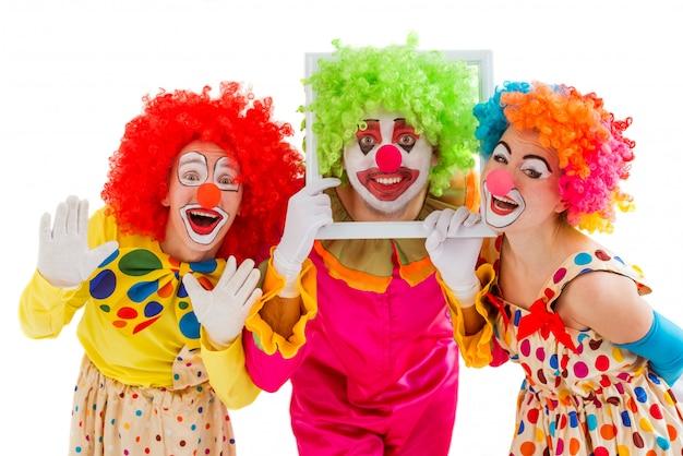 Drei spielerische clowns, die lustige gesichter machend halten.