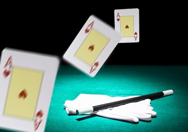 Drei spielkarten in luft über dem paar weißer handschuhe und zauberstab auf grünem hintergrund verschieben