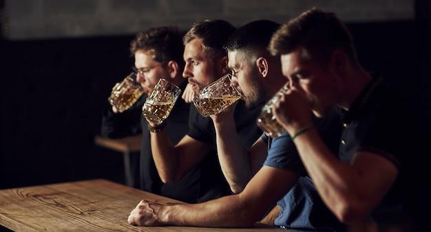 Drei sportfans in einer bar beim fußball gucken