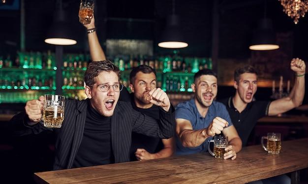 Drei sportfans in einer bar, die fußball gucken. mit bier in der hand
