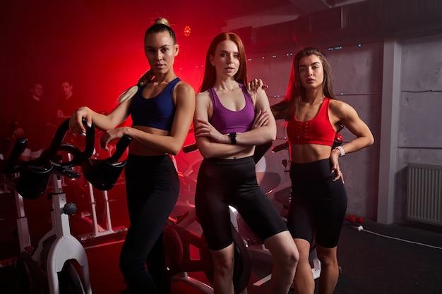 Drei sportliche sportlerinnen stehen zusammen in der nähe von stationären fahrrädern im fitnessstudio und posieren. isoliert in rotem neonbeleuchtetem raum in der wand