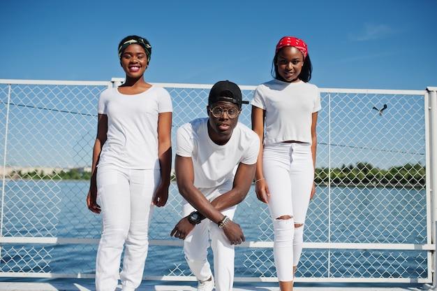 Drei stilvolle afroamerikanerfreunde, tragen auf weißer kleidung am pier auf strand gegen käfig. straßenmode von jungen schwarzen. schwarzer mann mit zwei afrikanischen mädchen.