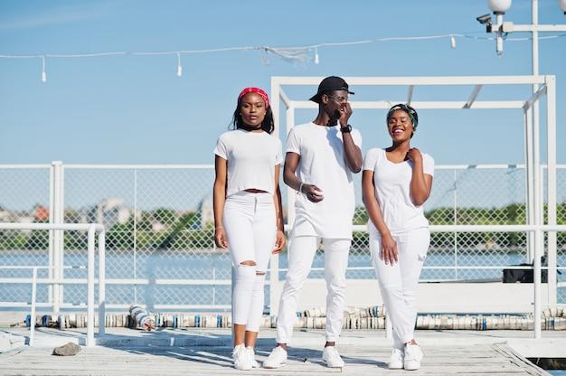Drei stilvolle afroamerikanerfreunde, tragen auf weißer kleidung am pier auf strand. straßenmode von jungen schwarzen. schwarzer mann mit zwei afrikanischen mädchen.