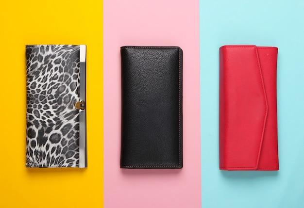 Drei stilvolle brieftaschen auf farbig. modischer minimalismus.