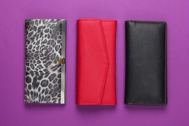 Drei stilvolle geldbörsen auf lila. modischer minimalismus.