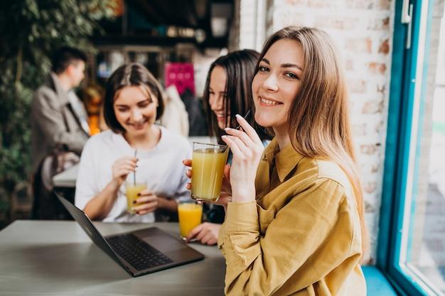 Drei studenten, die für prüfung mit laptop in einem café sich vorbereiten