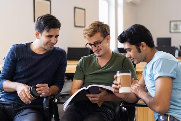 Drei studenten, die zusammen lehrbuch lesen und trinken