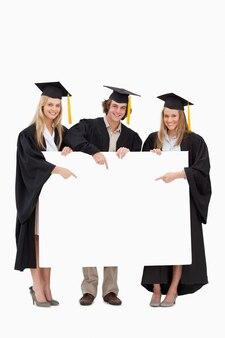 Drei studenten in der graduierten robe, die ein leeres zeichen hält und zeigt
