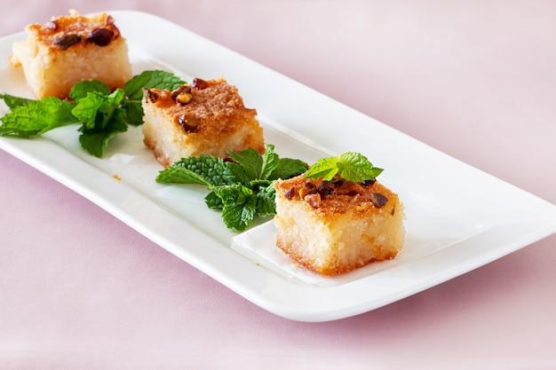Drei stück basbousa oder namoora traditionelles arabisches dessert. köstlicher hausgemachter grießkuchen mit nüssen auf weißem teller.