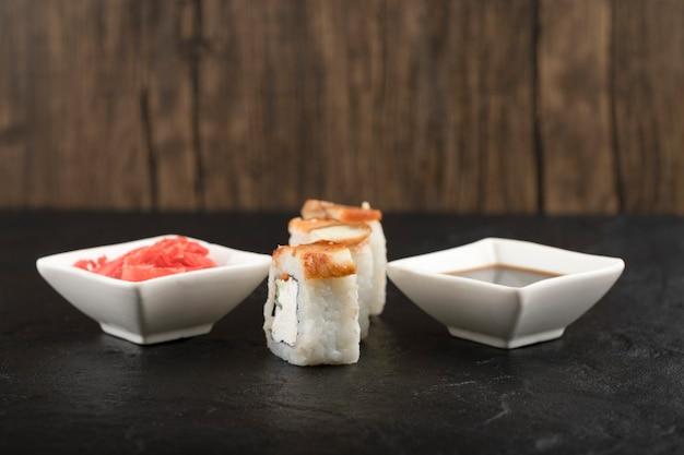 Drei stück drachen-sushi-rollen mit ingwer und soja auf schwarzer oberfläche