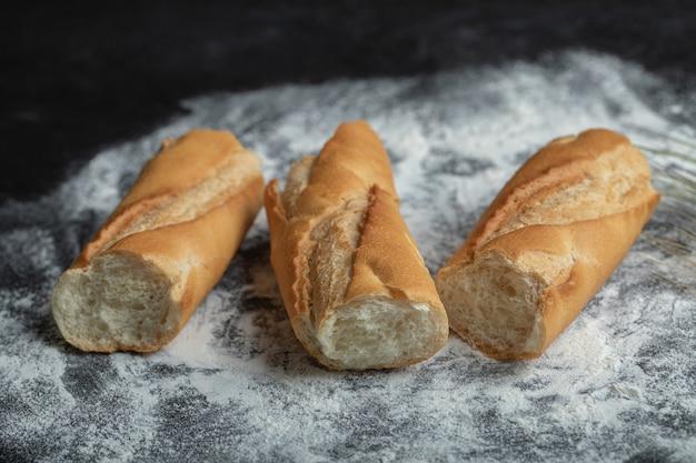 Drei stück frisches baguette auf mehl.
