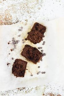 Drei stücke bananenbrot mit schokolade über einem ofenpapier