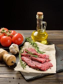 Drei stücke rohes rindfleisch auf einem schneidebrett. tabelle mit zutaten zum kochen von steak auf schwarzem hintergrund.