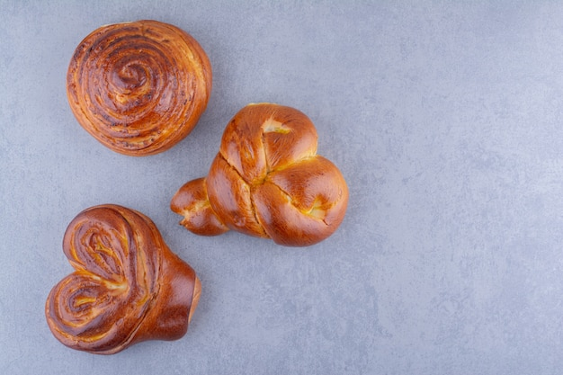 Drei süße brötchen auf marmoroberfläche angeordnet