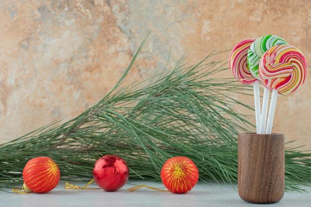 Drei süße bunte lutscher mit drei weihnachtskugeln auf marmorhintergrund. hochwertiges foto