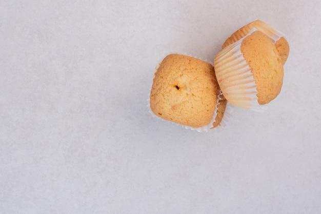 Drei süße cupcakes auf weißer oberfläche