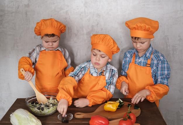 Drei süße europäische jungen in orangefarbenen kostümen kochen einen gemüsesalat. ein familienessen kochen