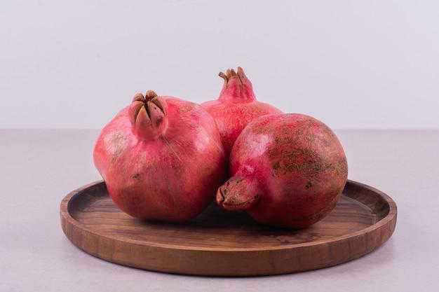 Drei süße granatapfel auf holzbrett auf weiß.