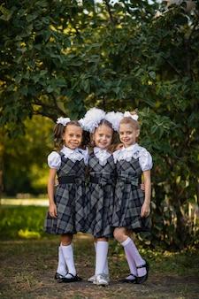 Drei süße junge mädchen in der schuluniform mit schwänzen und weißen schleifen, die am schulhof aufwerfen