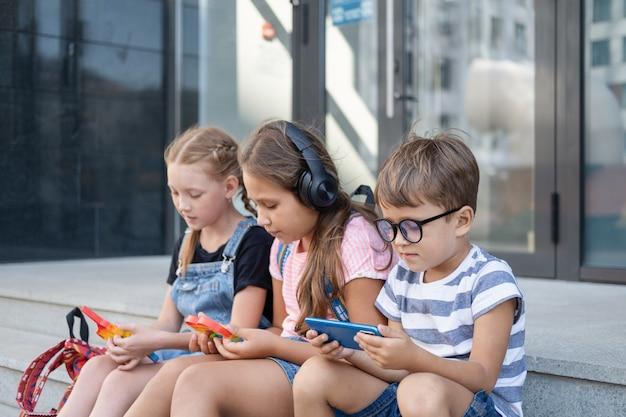 Drei süße kaukasische kinder mit kopfhörern und rucksack sitzen und spielen telefon. popit spielen. schulpause. streber. tag des wissens. nahaufnahme. zurück zum schulkonzept.