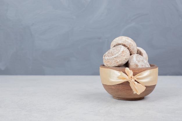 Drei süße kekse mit goldener schleife auf holzschale