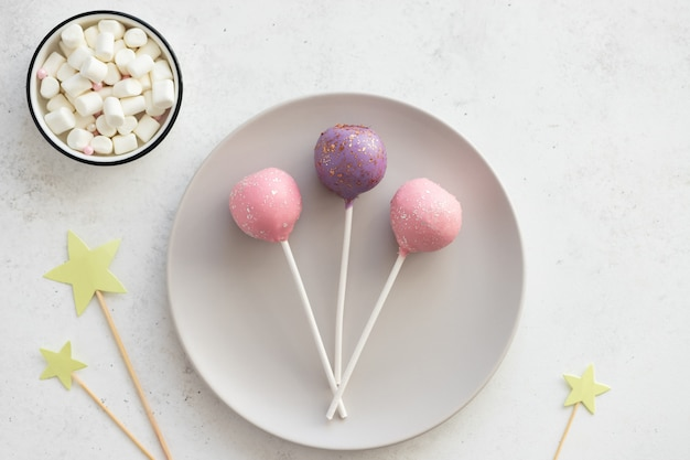 Drei süße kuchen knallen auf einem teller an einer weißen wand. dessert für kinderparty