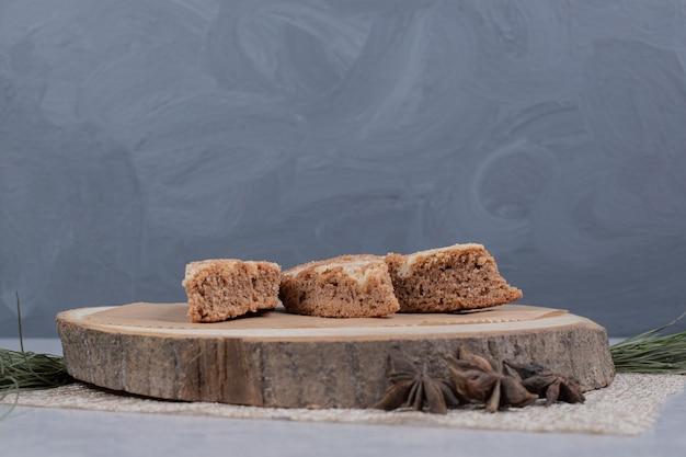 Drei süße scheiben kuchen mit sternanis auf holzteller. hochwertiges foto