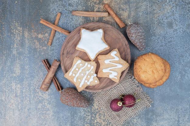 Drei süße weihnachtsplätzchen sterne auf holzplatte mit roten kugeln, tannenzapfen und zimtstangen.