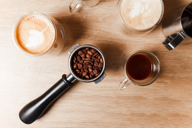 Drei tasse kaffee mit schritt durch kaffee mit bohnen auf dem tisch.