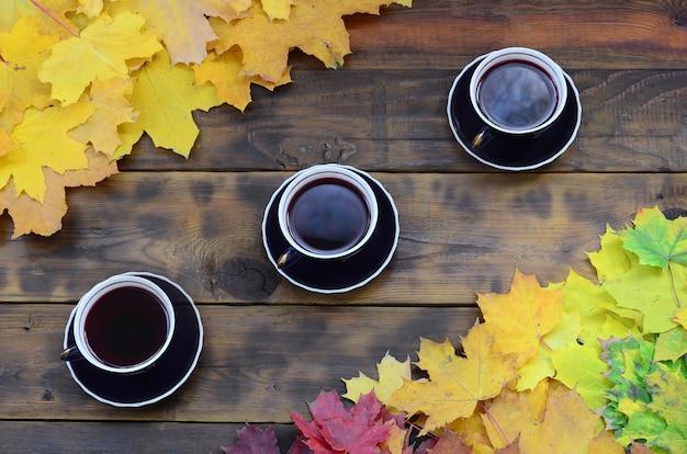 Drei tassen tee unter einem satz vergilbten gefallenen herbstlaubs auf einer hintergrundoberfläche von natürlichen hölzernen brettern der dunkelbraunen farbe