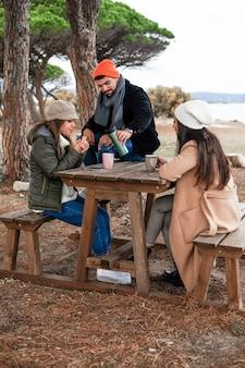 Drei tausendjährige freunde, die im winter draußen sitzen und sich auf holztisch im kiefernwald verbinden - leute wärmen draußen, die heißen tee im kalten winterklima trinken
