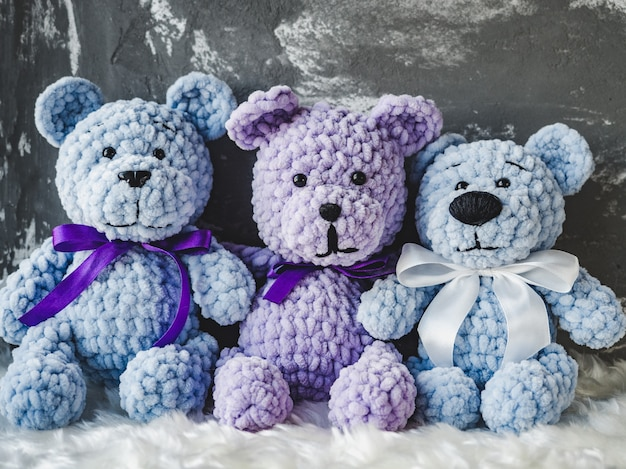 Drei teddybären sitzen auf einem weißen plaid Premium Fotos