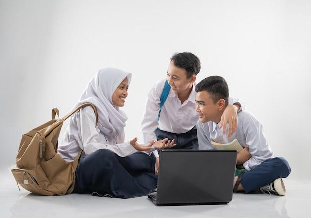 Drei teenager in junior-high-school-uniformen unterhalten sich, während sie auf dem boden sitzen und einen laptop benutzen...