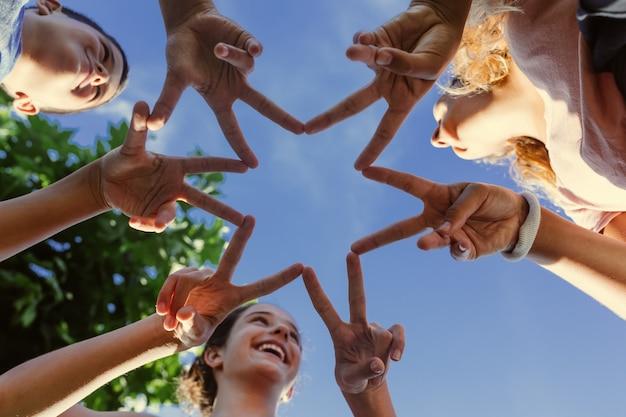 Drei teenager lachen, als sie mit ihren händen einen stern bilden