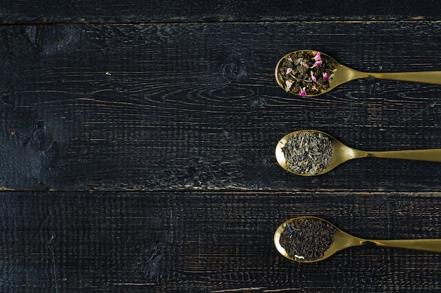 Drei teesorten in löffeln - grün, schwarz und rooibos