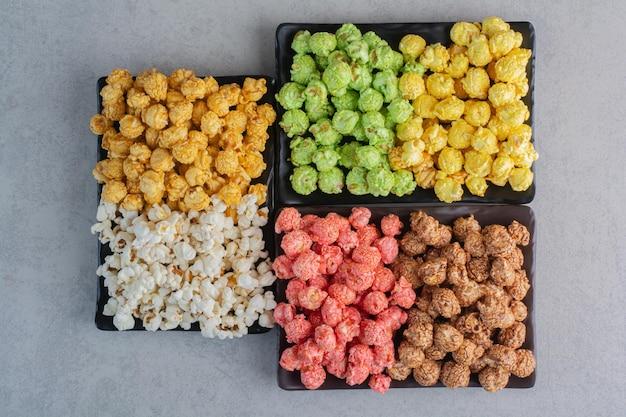 Drei teller mit verschiedenfarbigen popcorn-bonbons und einfachem popcorn auf marmoroberfläche