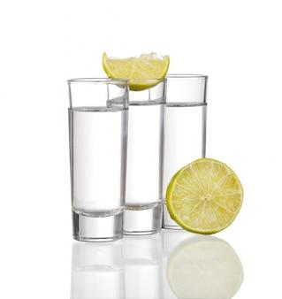 Drei tequila-schüsse mit kalk lokalisiert auf weißem hintergrund