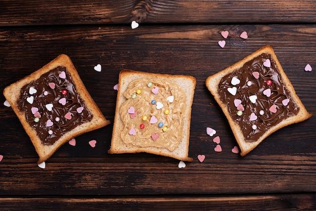 Drei toast mit schokoladenpaste und erdnussbutter, bestreut mit bunten herzen auf dunklem holzhintergrund.