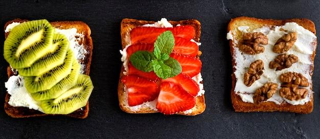 Drei toasts mit mildem hüttenkäse, erdbeeren, kiwi und nüssen