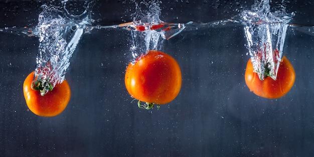 Drei tomaten in wasser getaucht