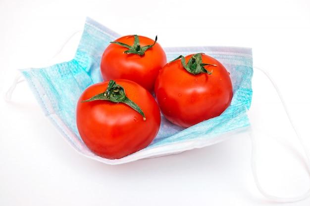 Drei tomaten liegen auf einer medizinischen schutzmaske. landwirtschaftliche krise im zusammenhang mit der coronavirus-pandemie.