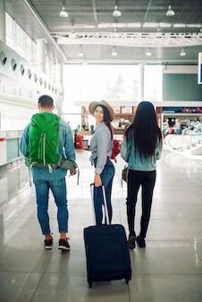 Drei touristen mit gepäck im flughafen, rückansicht. passagiere mit gepäck im flugterminal