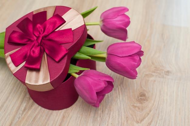 Drei tulpen und eine rote schachtel als geschenk in form eines herzens am valentinstag