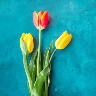 Drei tulpenblumen auf blauer tabelle