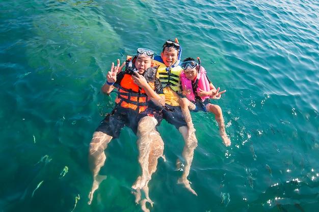 Drei typen, die glücklich im meerwasser schwimmen