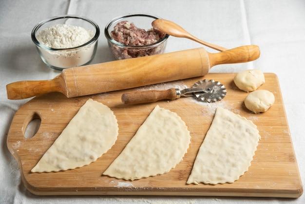 Drei ungekochte fleischgutabs auf holzbrett. aserbaidschanische nationale küche.